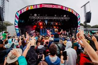 """May be an image of one or more people, people playing musical instruments, people standing, crowd, outdoors and text that says """"STANDON CALLING"""""""