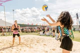 May be an image of one or more people, people standing, people playing volleyball, ball and beach