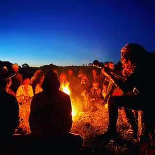 May be an image of one or more people, people sitting, fire and outdoors