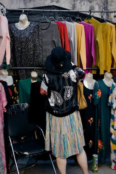 A woman shopping for clothes at a streetside store