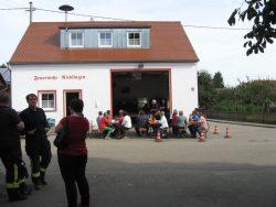 Die Besucher des Feuerlöscheraktionstages sitzen vor dem Feuerwehrhaus in Rieblingen.