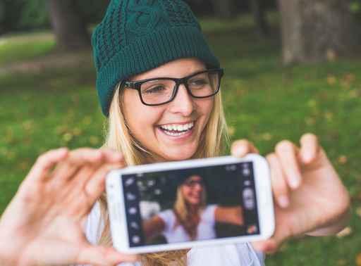 Blonde woman posing outdoor, taking self portrait