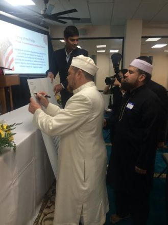 Imam Yasir Birgas signs the Pledge