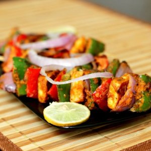 paneer tikka served with onion rings and a lemon wedge