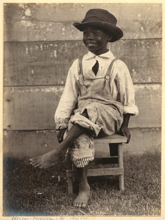 Young boy dawning a hat and overalls