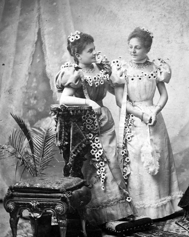 two women donning early 1900s fashion dresses
