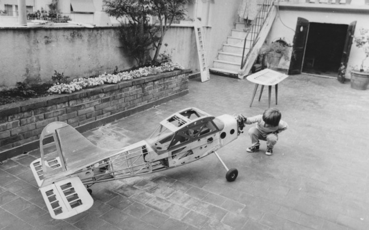 boy in the 1950s examining a small plane