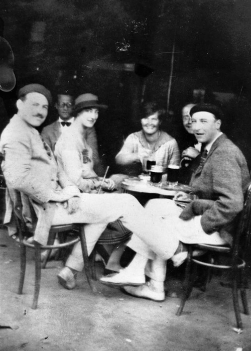 lost generation writer Ernest Hemingway sits with people at a table.