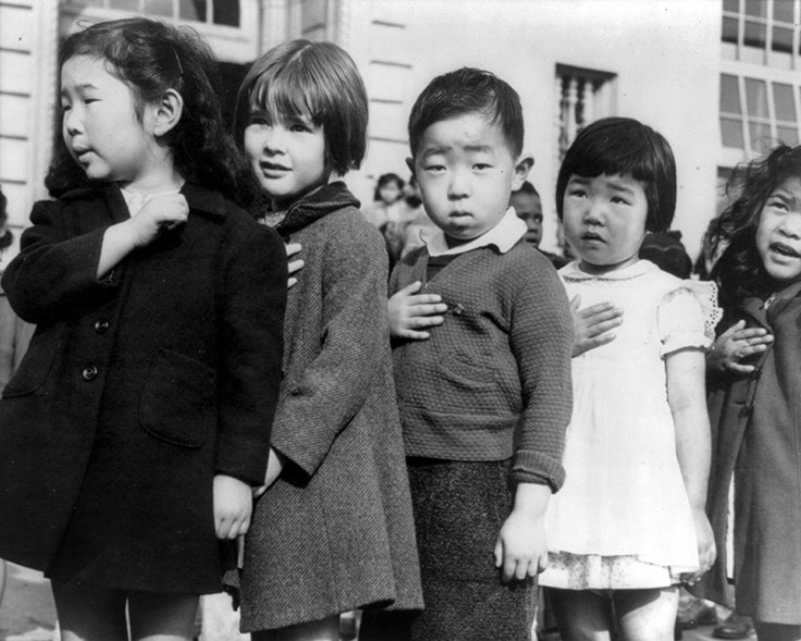 Japanese children hold their hands over their hearts and pledge allegiance to the united states during ww2.
