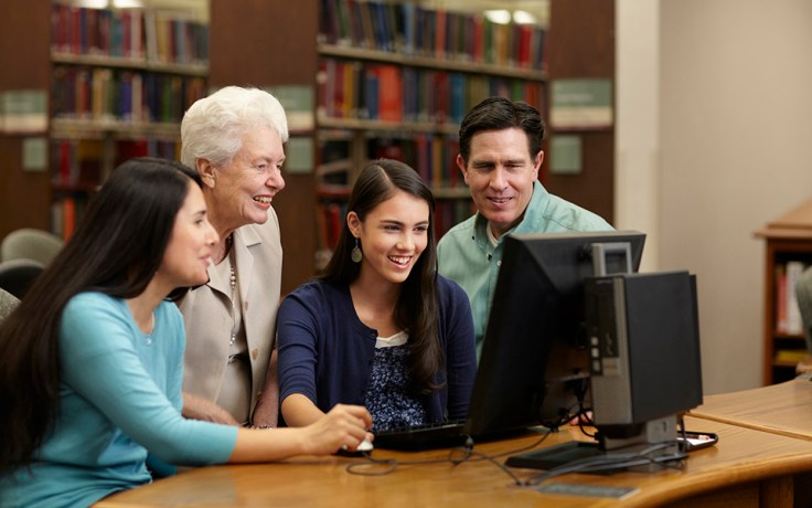 A family looks at a library computer.