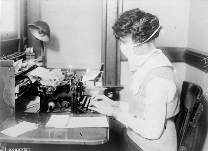 a woman wears a mask while she works during the 1918 Spanish Flu.