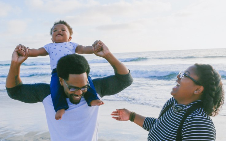 a family celebrates together on a beach.