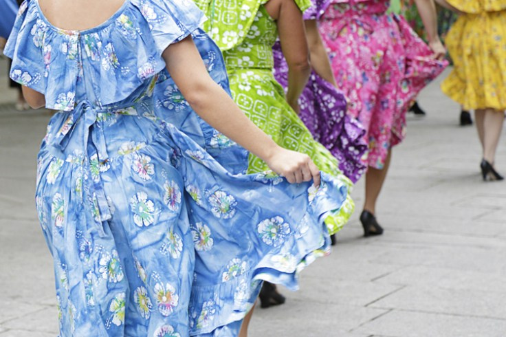 puerto rican women dance in cultural outfits.
