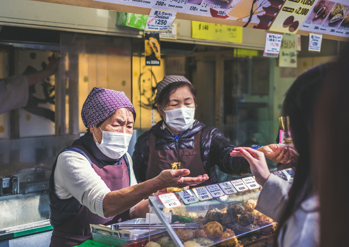 two women wear face coverings as they sell food.
