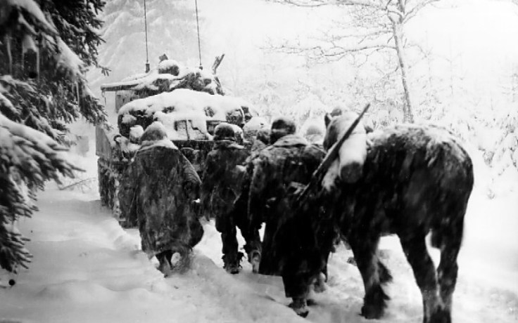 Soldiers walk in snow during Battle of the Bulge