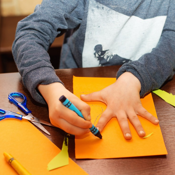 Child tracing his hand for a family tree.