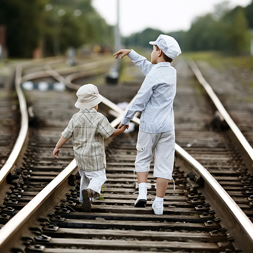 Two boys walking on train tracks that merge and split.