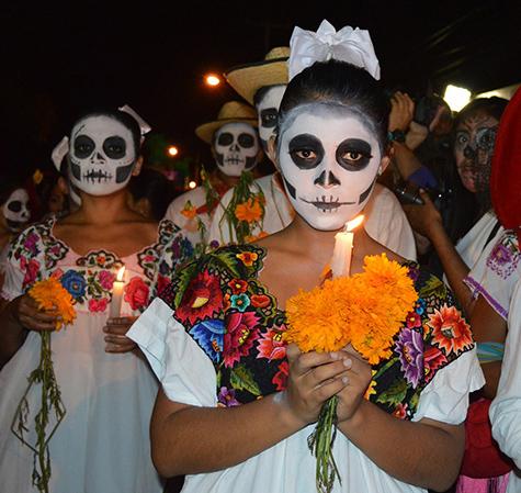 Una niña vestida para el Día de Muertos que sostiene una vela