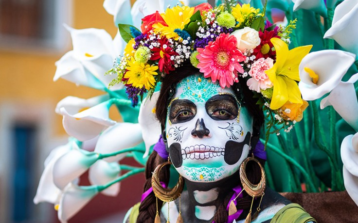 a woman wearing a colorful mask on dia de muertos