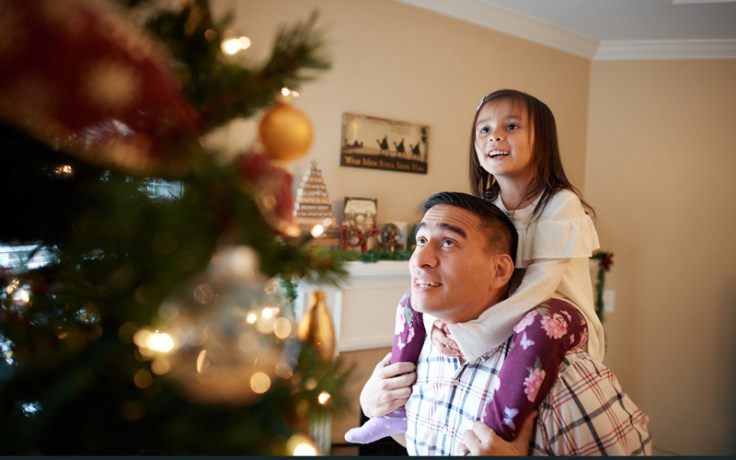a father and daughter decorate a christmas tree together.