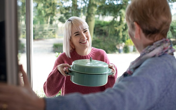Blonde woman bringing food to an elderly neighbor.