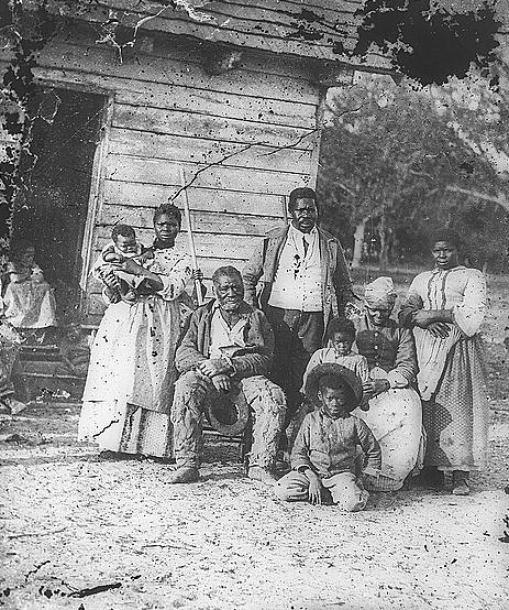 an enslaved family outside of their house.