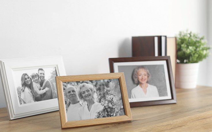 Three photographs on a table of a remembered loved one.