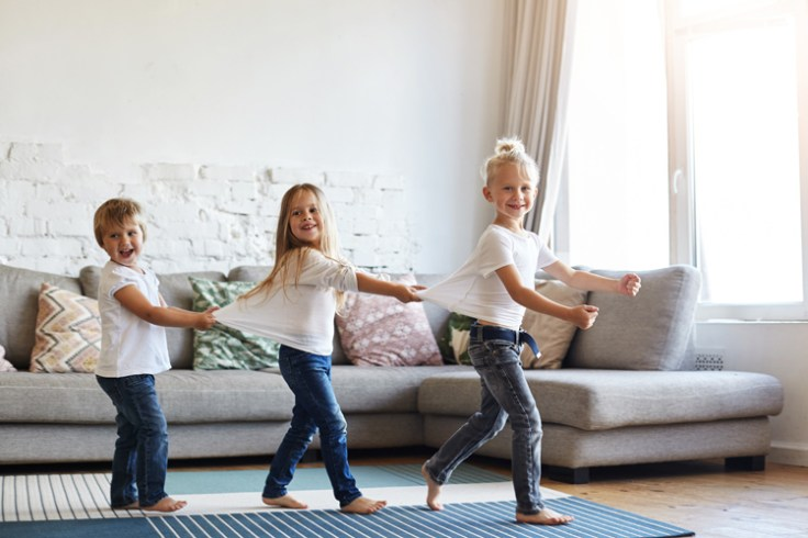Three children lined up holding each other's shirts in a living room.