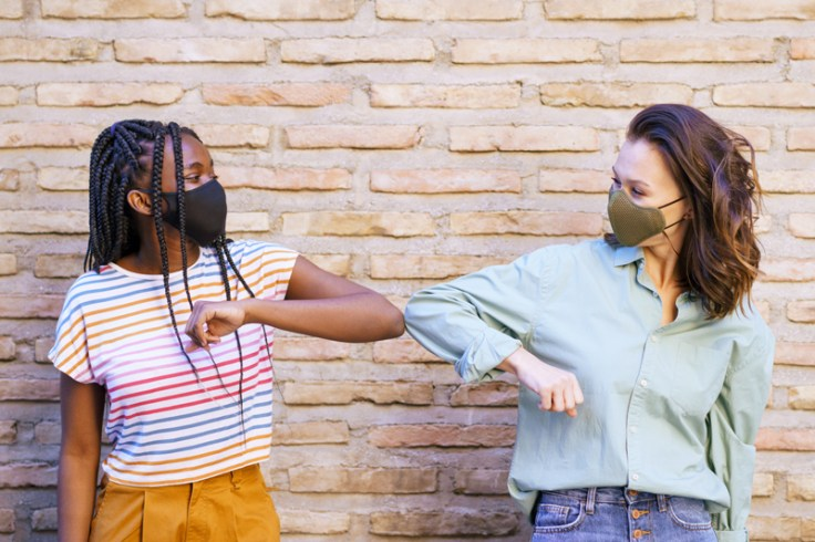 two generation z girls wearing a mask and touching elbows.