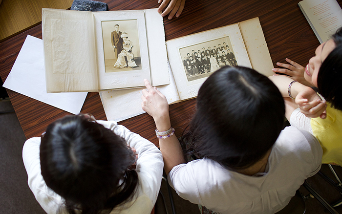 A mother and her daughter work to add memories to their family tree by going through old family photos.