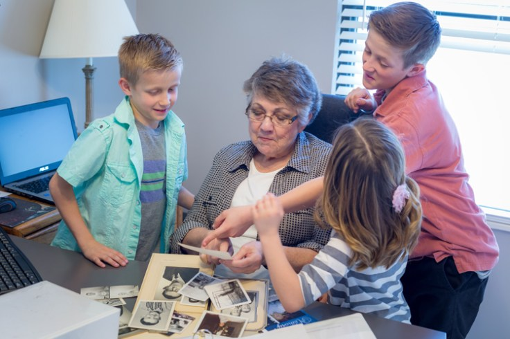 Grandmother showing pictures to grandchildren. Fun mother's day activity.