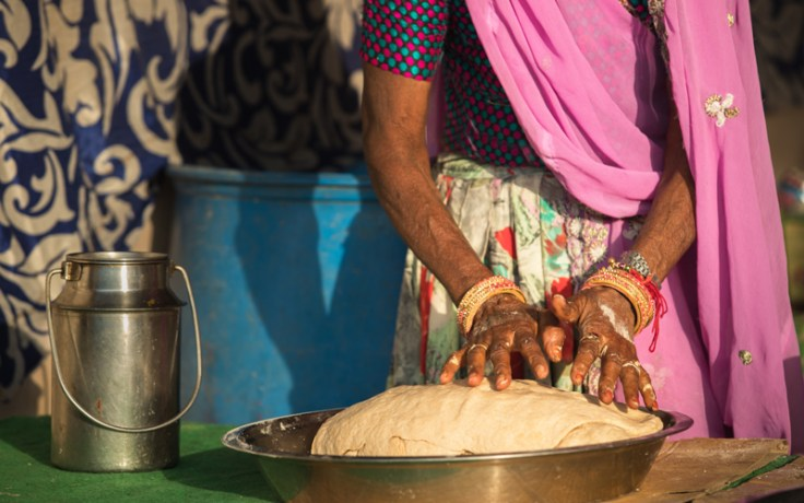 a woman makes a type of world cuisine bread.