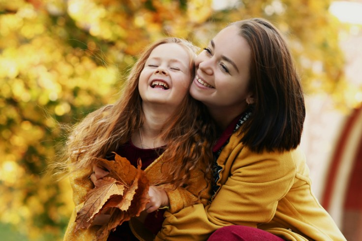 an irish mom and a little girl laugh together in the leaves.