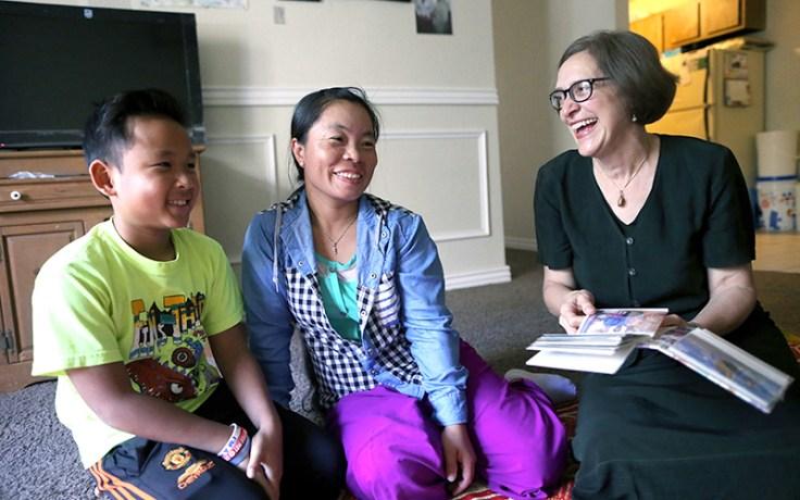 Una madre y su hijo se ríen con una mujer que tiene en las manos fotografías de familiares.