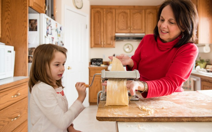 Girl and grandmother make noodles together and explore heritage together