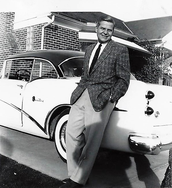stylist 1950s man stands next to car