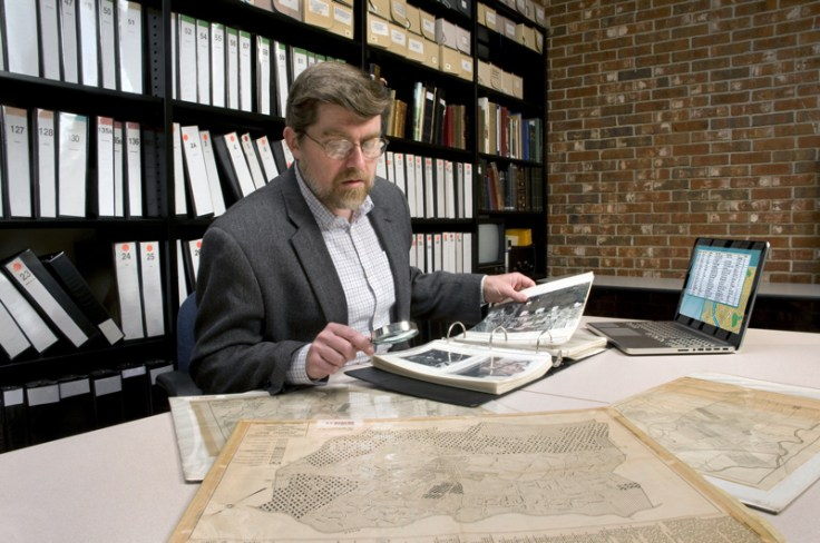 A man looks at maps in a library.