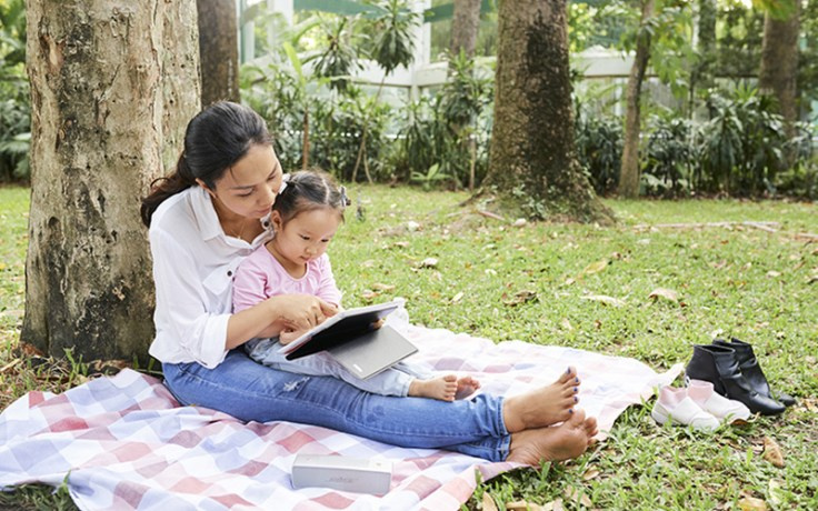 a mother and daughter sit under a tree and use a tablet.