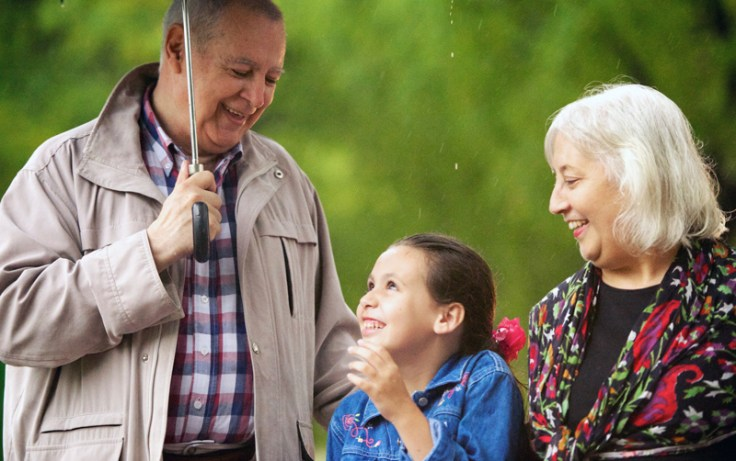Grandparents holding an umbrella with a little girl.
