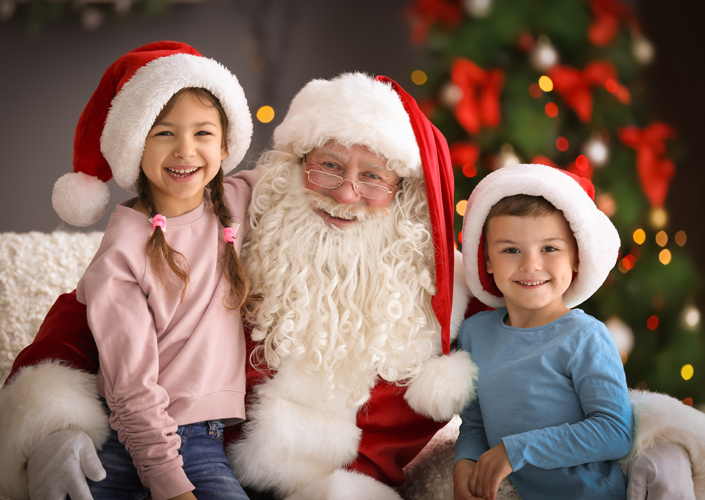Two children smiling with Santa Claus.