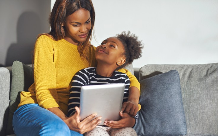 an african american woman and her daughter read on a tablet together