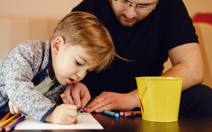 Little boy draws while father helps him
