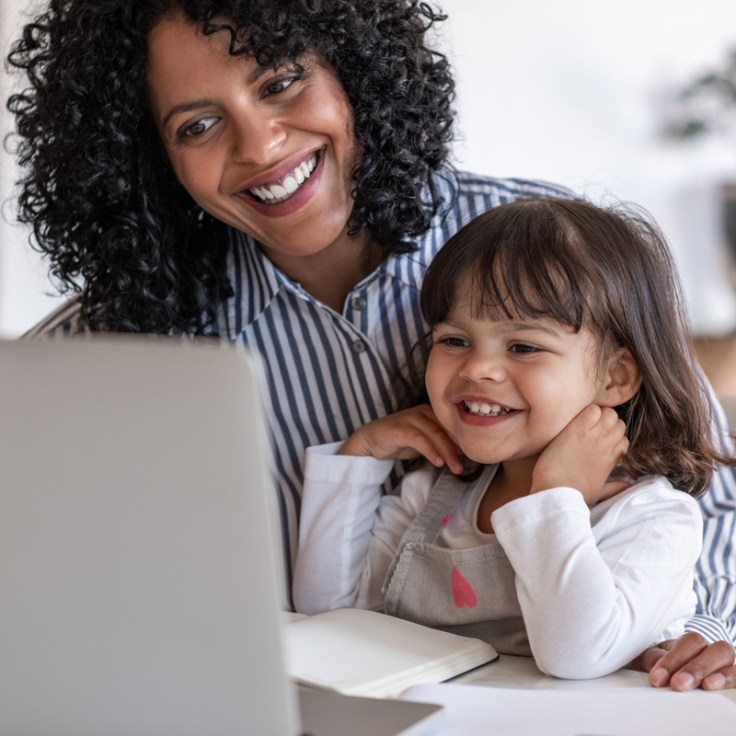 Mother and daughter looks at computer together while doing an activity