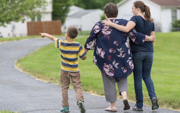Grandmother and grandchildren walk down path.