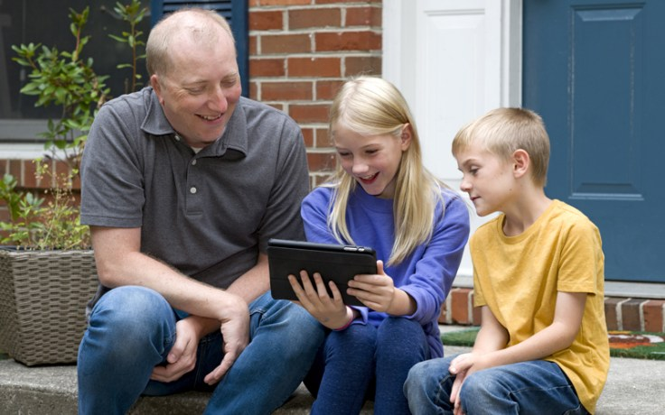 a father plays on a tablet with his children.