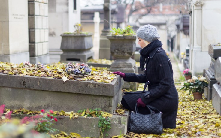Woman puts hand on ancestor's gravestone