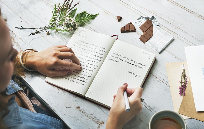 a woman starts her journal.