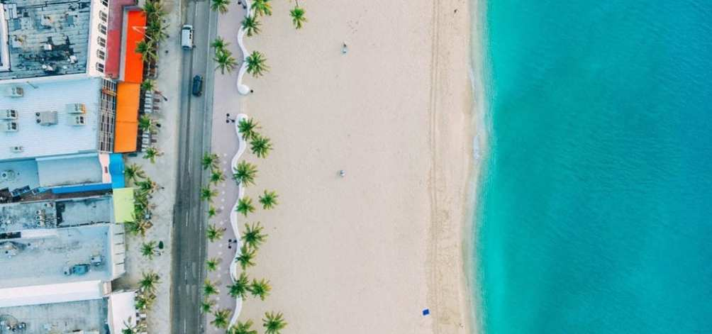 A top-down view of the beach and a nearby road in the Cayman Islands.