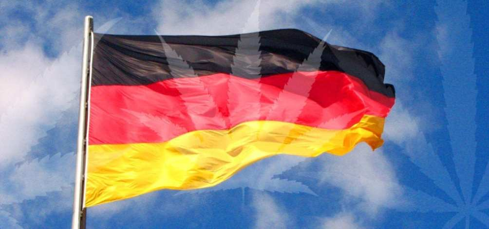 The flag of Germany with a misty cannabis leaf collage spliced over the top.