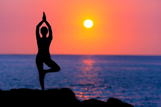 Silhouette of a person doing yoga next to the water